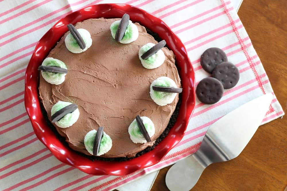 Thin Mint No-Bake Chocolate Cheesecake in a red pie pan garnished with whipped cream, green sprinkles and whole thin mint cookies