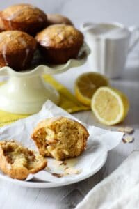 a Citrus Almond Muffin split in half so the inside is visible and a pale yellow cake pedestal with a stack of muffins in the background