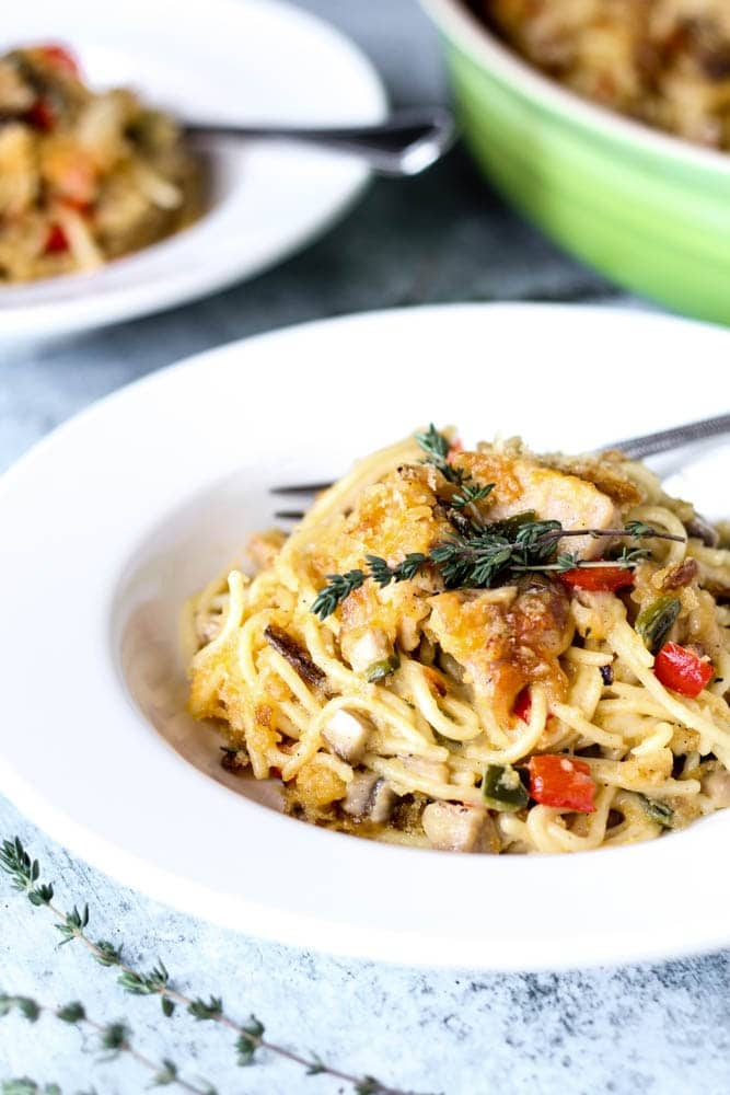 bowl of Chicken Spaghetti or spaghetti noodles covered in a mushroom cream sauce with chicken, onions and peppers and topped with melted cheddar, breadcrumbs, and crispy jalapenos