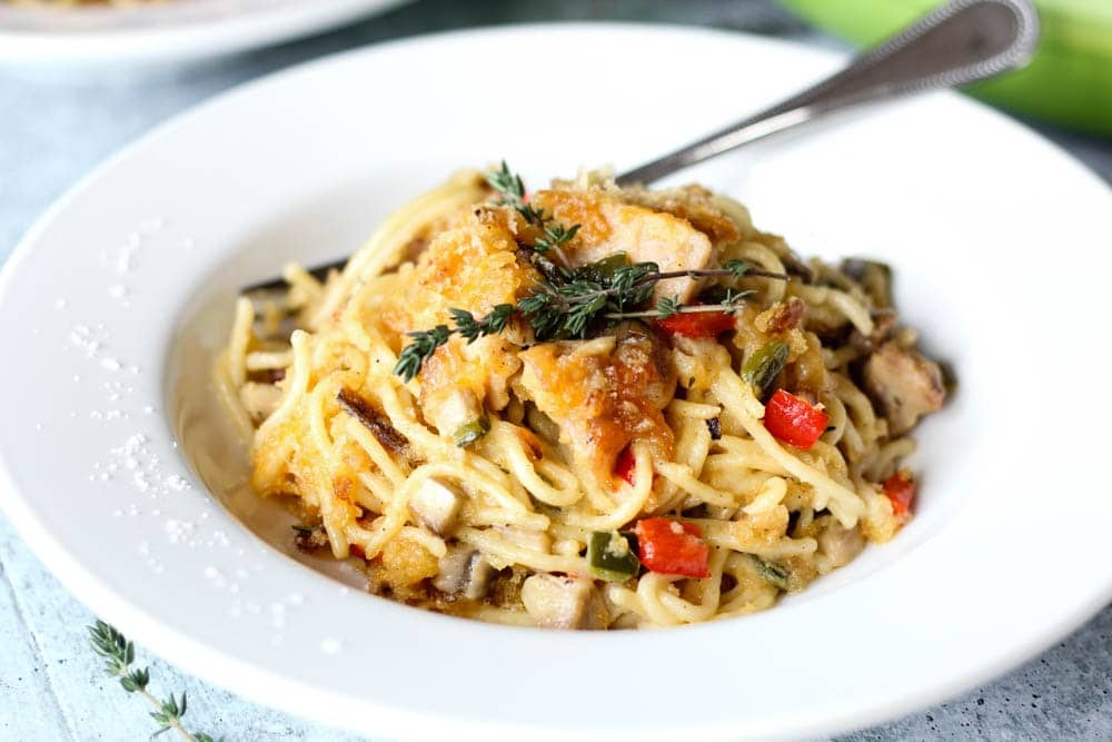 a bowl of Chicken Spaghetti or spaghetti noodles covered in a mushroom cream sauce with chicken, onions and peppers and topped with melted cheddar, breadcrumbs, and crispy jalapenos
