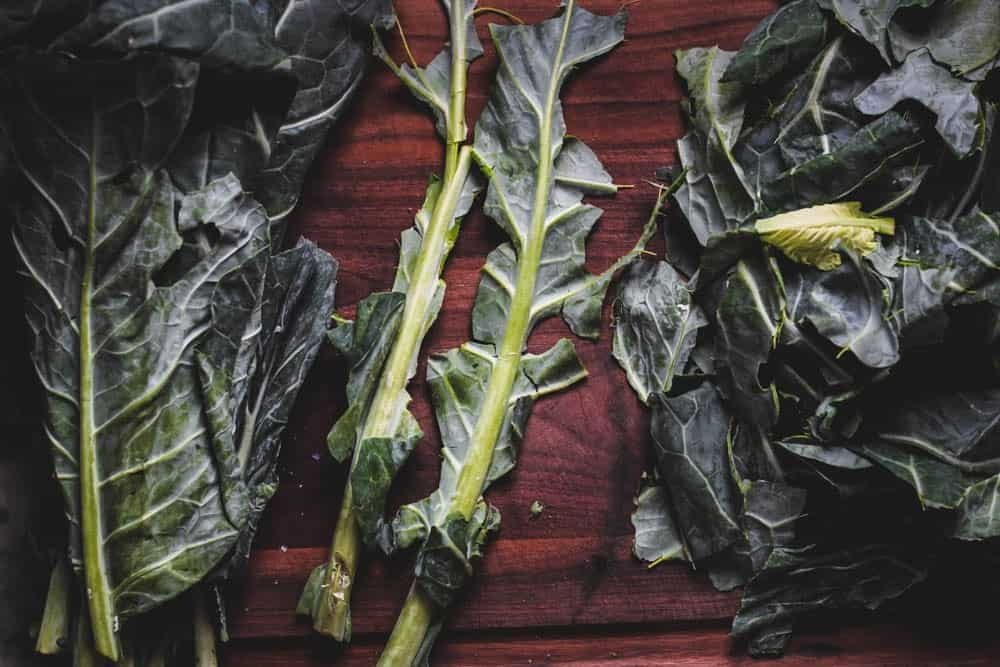 collard greens with the vein removed on a dark wooden cutting board