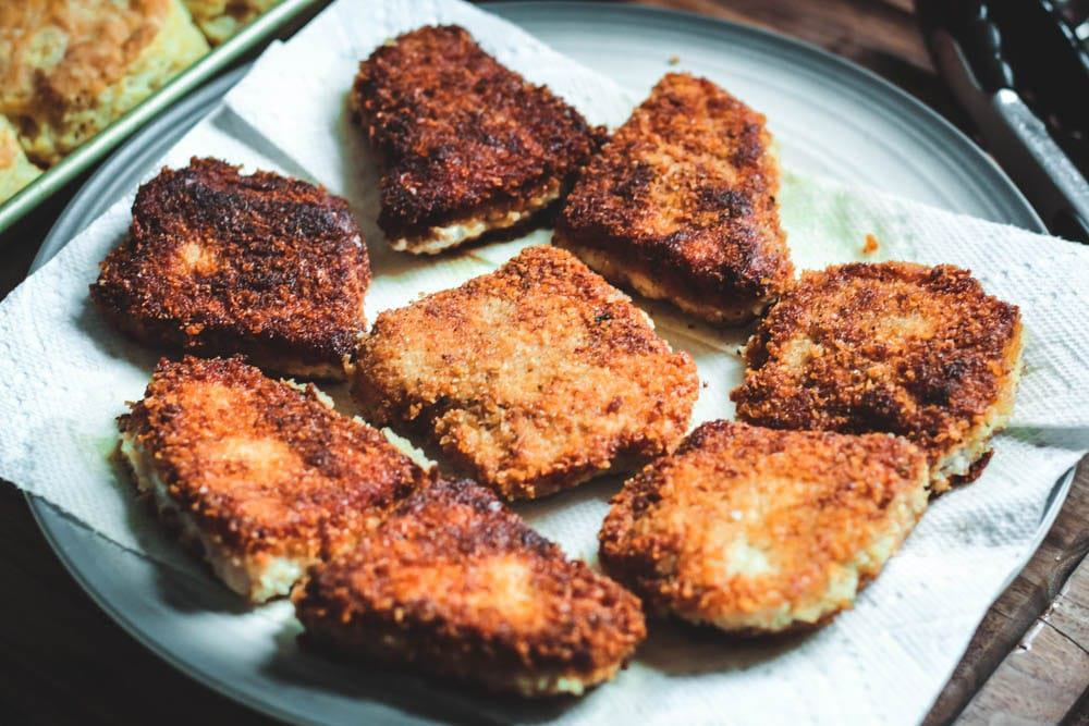golden brown fried pork chops on a plate with a paper towel to capture excess grease