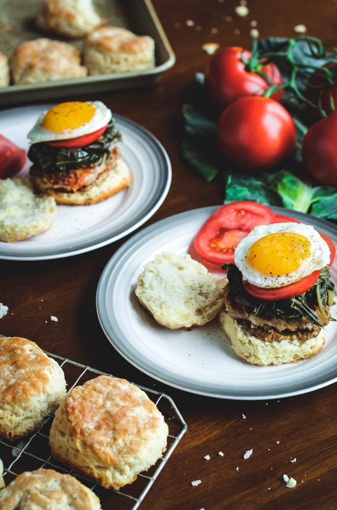 Two Pork and Collard Greens Biscuit Sandwiches served open face to show the sunny side up egg and served with sliced tomato