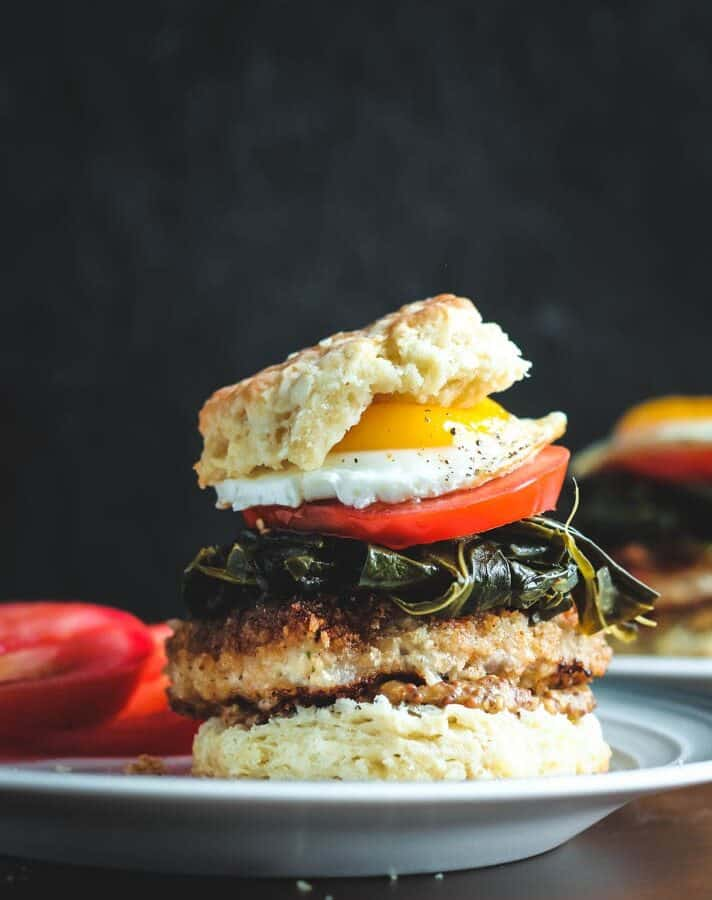 Pork and Collard Greens Biscuit Sandwich with layers of biscuit, whole grain mustard, fried pork chop, cooked collard greens, sliced tomato and a sunny side up egg