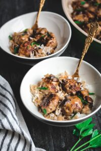 Poor Boy Supper or meatballs in a mushroom gravy over white rice served into two bowls with gold forks