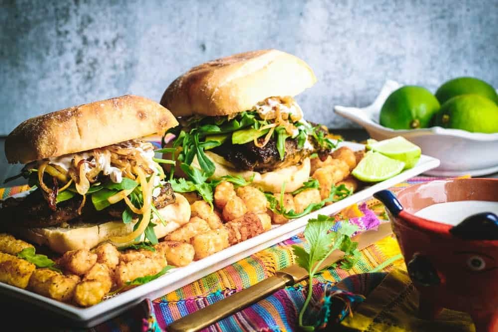 Cilantro Chicken Sandwiches with Chili-Spiced Tater Tots on a long rectangular white plate with a bowl of limes in the background