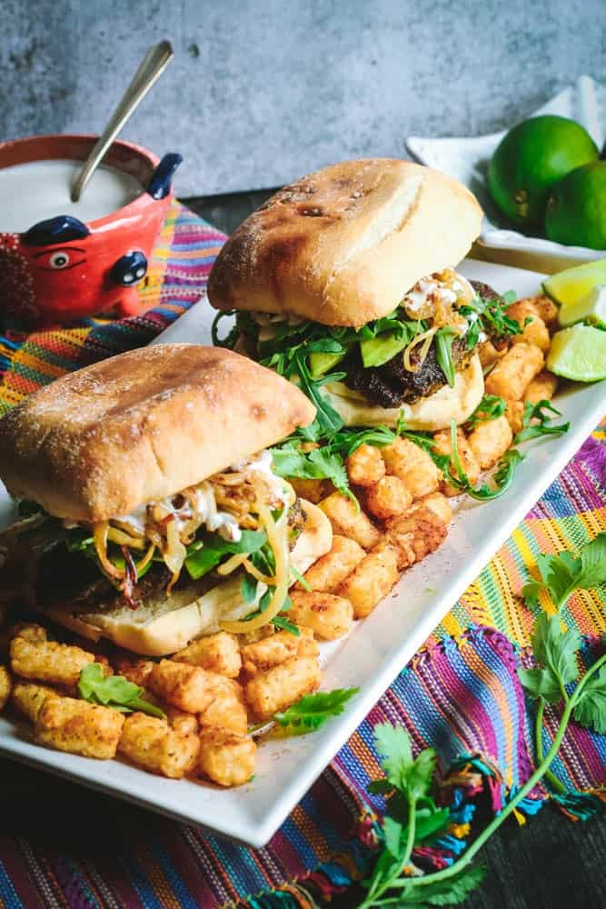 Cilantro Chicken Sandwiches with Chili-Spiced Tater Tots on a long rectangular white plate