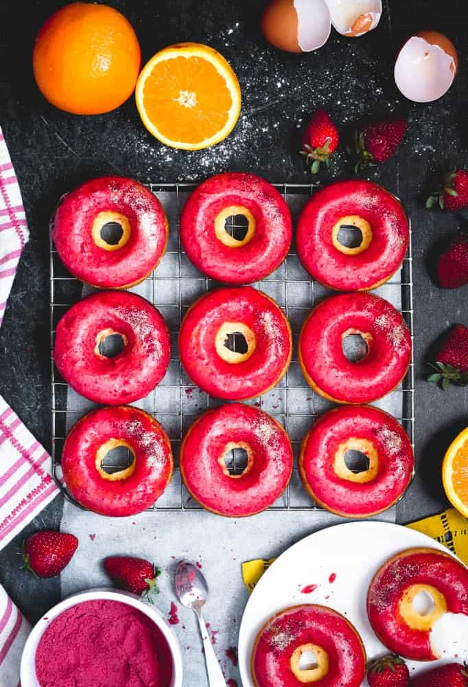 overhead view of orange donuts with strawberry glaze on a cooling rack with fresh strawberries and oranges