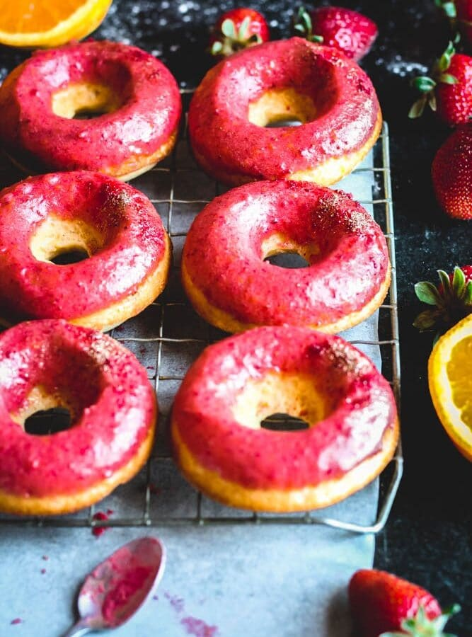 closeup shot of orange donuts with strawberry glaze on a cooling rack with fresh strawberries and oranges
