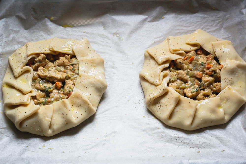 uncooked chicken potpie crostata on a baking sheet lined with parchment paper ready for the oven