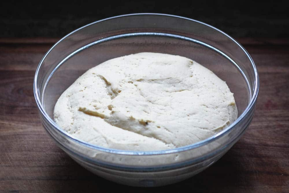 closeup of risen pizza dough in a glass bowl