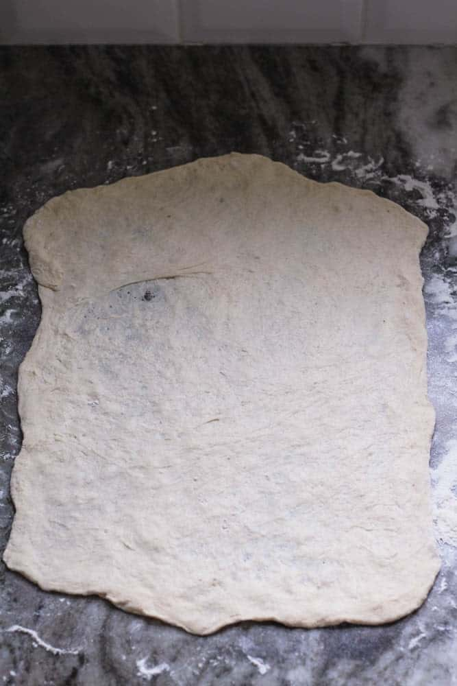 raw pizza dough for stromboli spread as thin as possible in a rough rectangular shape