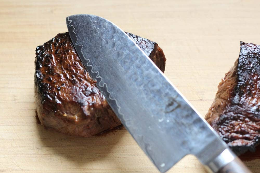 closeup shot of steak with chef's knife showing the direction of the grain of the meat