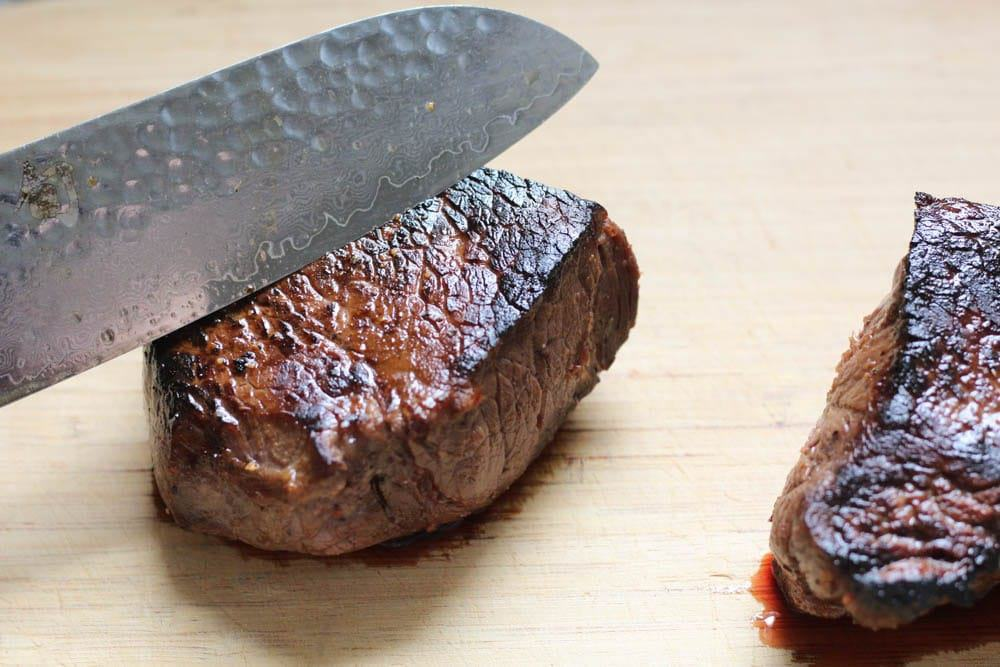 closeup shot of a cooked steak on a cutting board with a chef's knife indicating how to cut against the grain of the meat