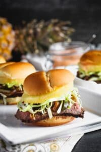 closeup shot of teriyaki steak and pineapple sliders with shredded cabbage peaking out