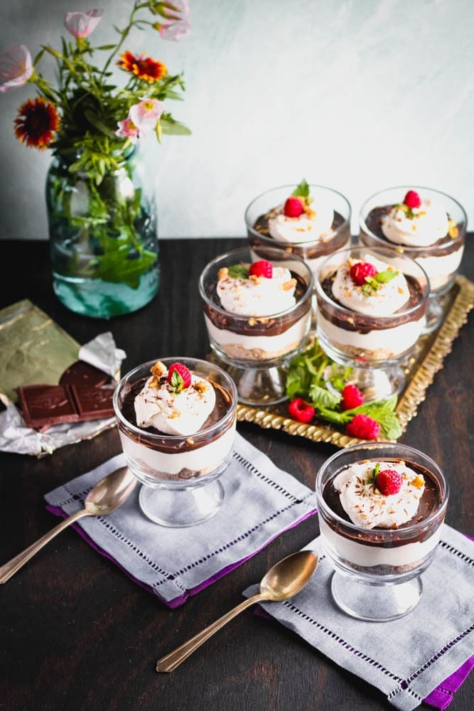 overhead shot of Chocolate Cheesecake Trifles layered in individual trifle dishes served with fresh raspberry and mint as garnish and fresh flowers in the background