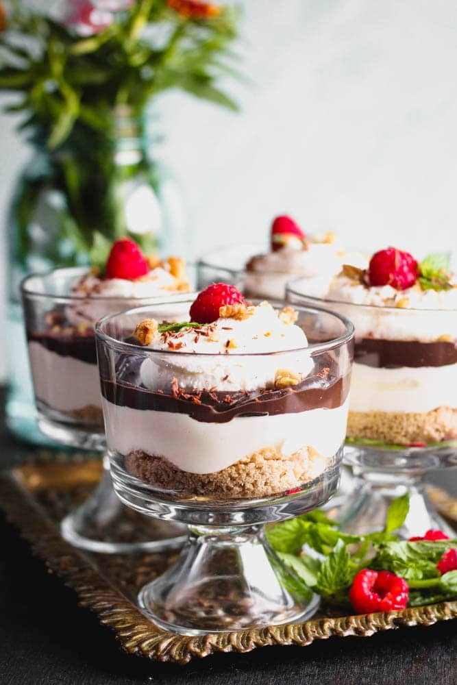 closeup shot of Chocolate Cheesecake Trifles layered in individual trifle dishes served with fresh raspberry and mint as garnish