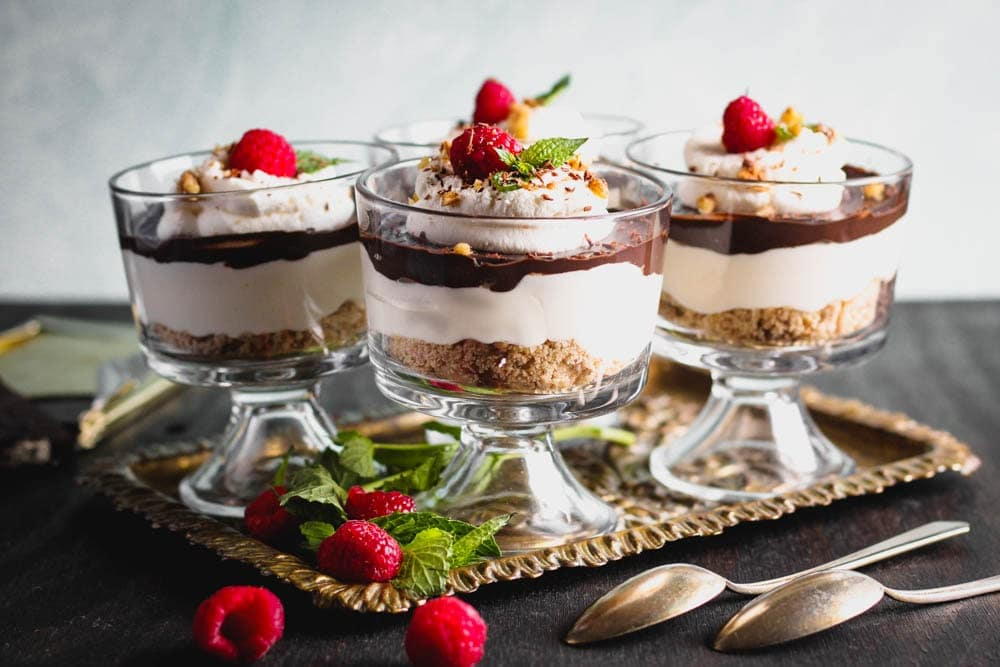 Chocolate Cheesecake Trifles layered in individual trifle dishes served with fresh raspberry and mint as garnish