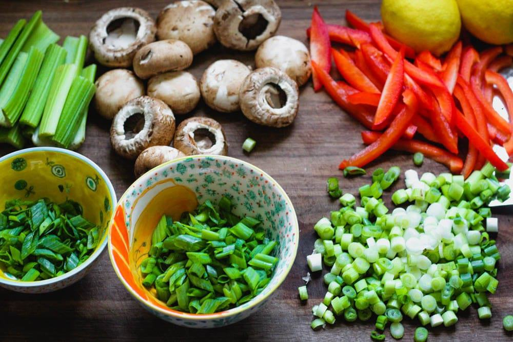 celery, mushrooms, bell pepper, lemon and green onions being prepared on a wooden cutting board