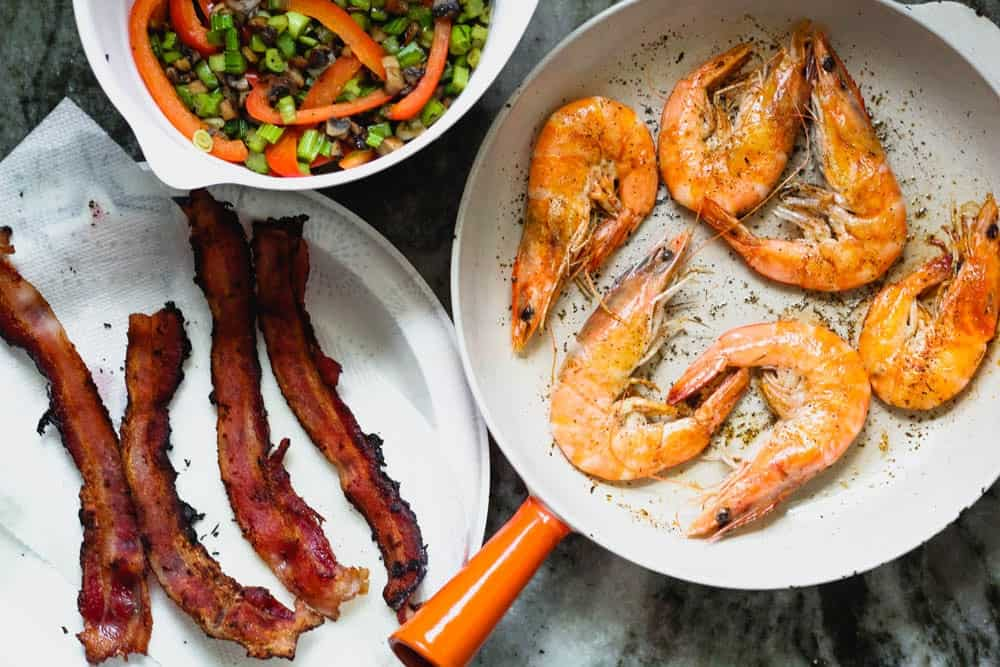 Cooked bacon draining on a paper towel next to a saute pan of cooked head-on shrimp