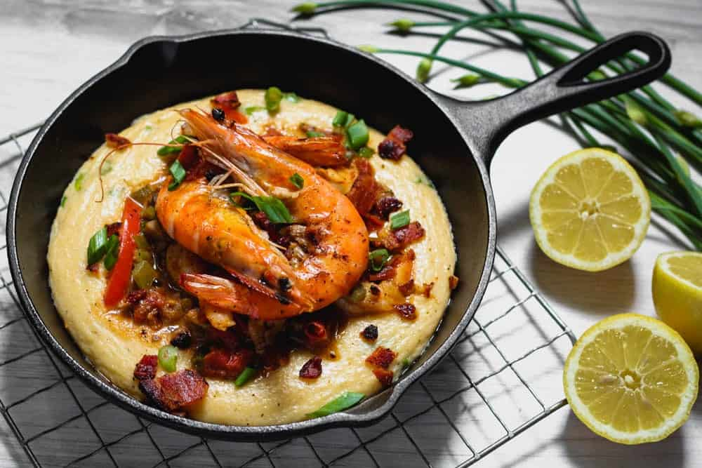 a cast iron skillet filled with grits topped with bacon, red bell pepper, mushrooms, green onions, shrimp and a rich New Orleans style barbecue sauce with a side of halved lemons