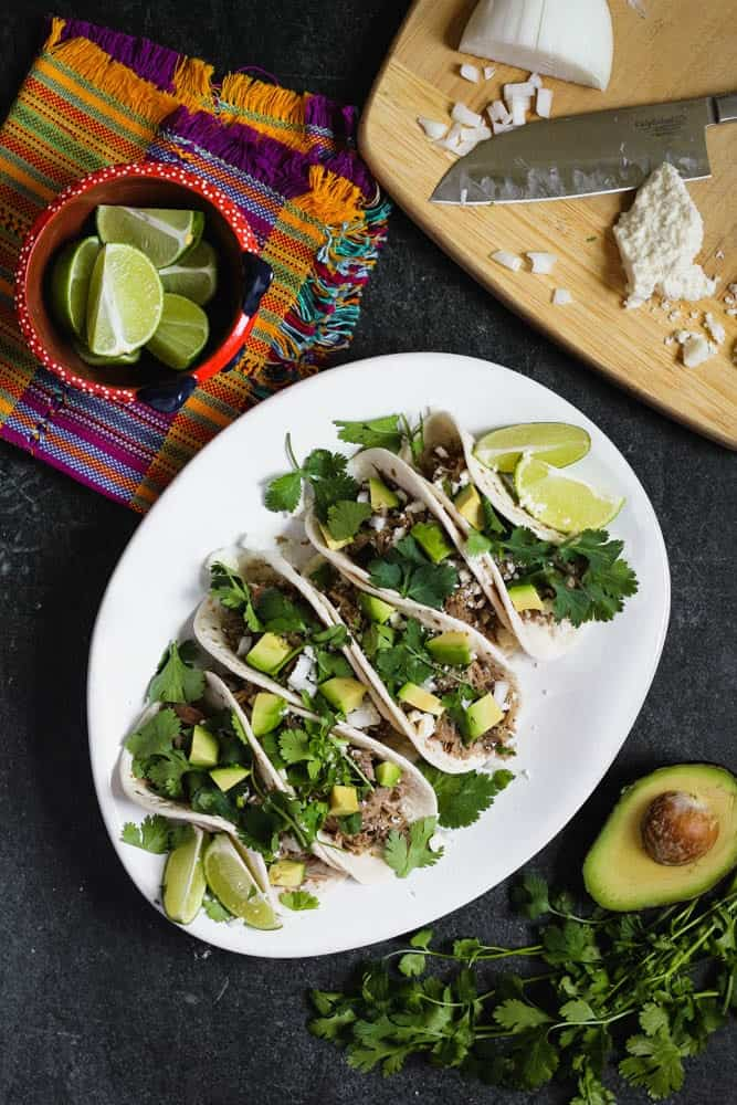 overhead shot of braised salsa verde pork tacos on flour tortillas topped with cilantro and diced avocado