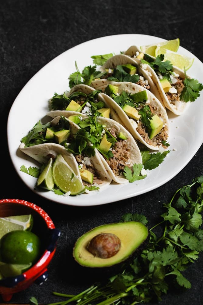 braised salsa verde pork tacos on flour tortillas topped with cilantro and diced avocado
