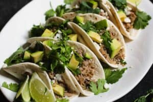 closeup shot of braised salsa verde pork tacos on flour tortillas topped with cilantro and diced avocado
