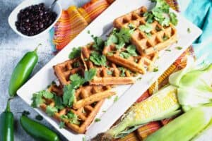 a long rectangular plate of black bean and corn waffles topped with cilantro and a small bowl of black beans on the side