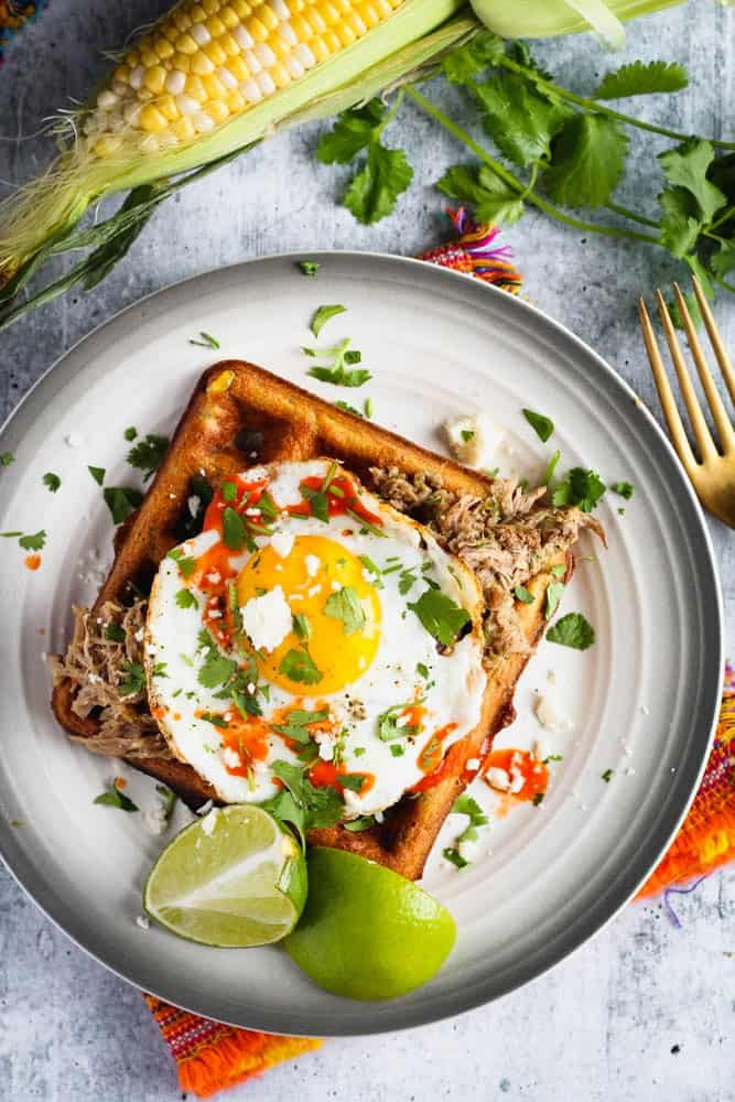 black bean and corn waffle on a small plate topped with a sunny side up egg and cilantro and a side of lime