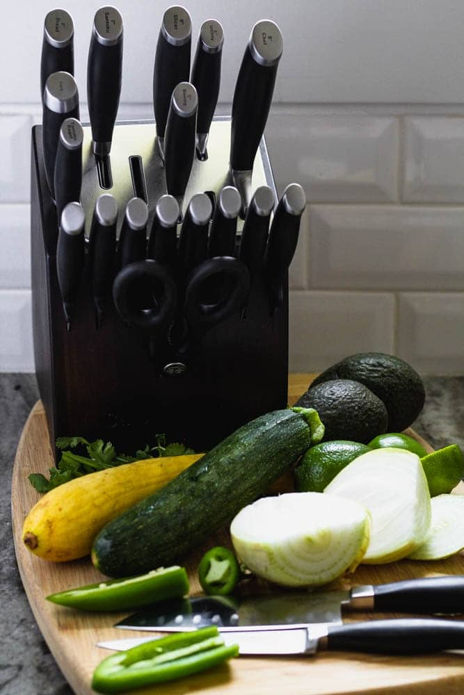 cutting board filled with jalapenos, onion, squash and avocado before preparing for the recipe alongside a Calphalon self-sharpening knife set