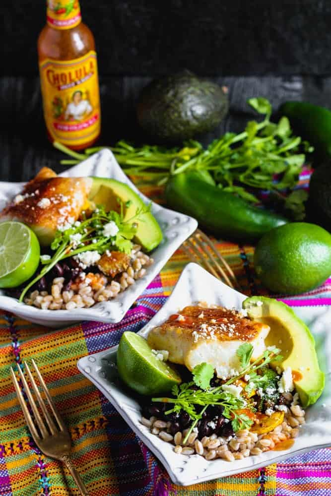 Two bowls of cooked farro topped with taco seasoned cod, fresh avocado, lime, black beans, cilantro and cooked vegetables with hot sauce and lime in the background