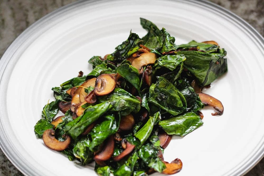 browned sliced mushrooms and charred greens on a dinner plate