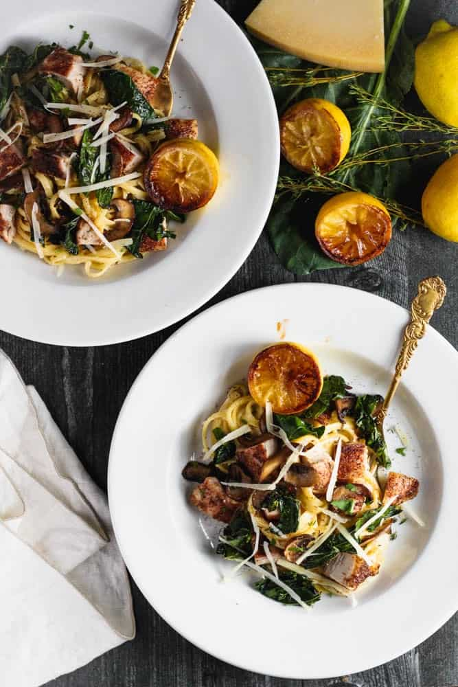 Two bowls of chicken alfredo with charred greens and lemons