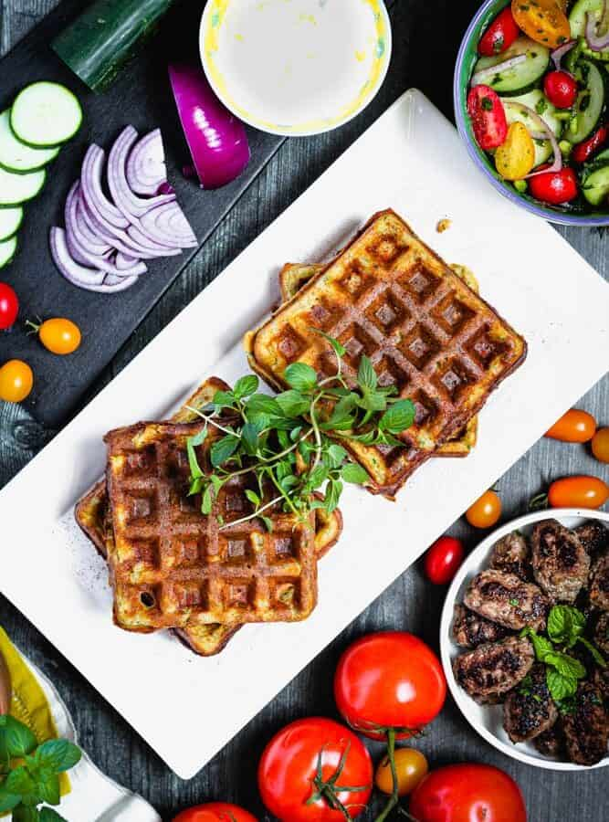 overhead shot of falafel waffles topped with fresh mint and surrounded by red onions, tomatoes and lamb sausage