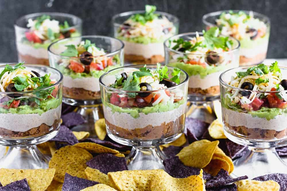 individual sever layer dips in small trifle dishes with blue and yellow corn tortilla chips scattered around