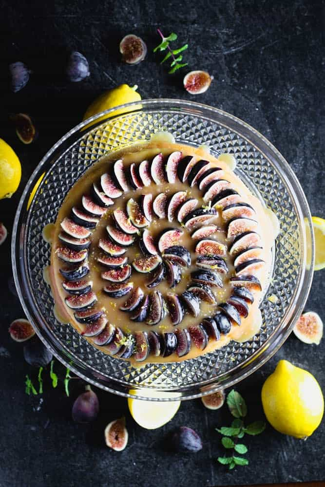overhead shot of lemon yogurt cake topped with honey caramel and quartered figs on a crystal cake pedestal with lemons and figs in the background