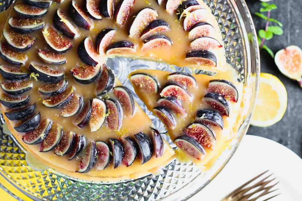 closeup overhead shot of lemon yogurt cake topped with honey caramel and quartered figs on a crystal cake pedestal with one slice being removed