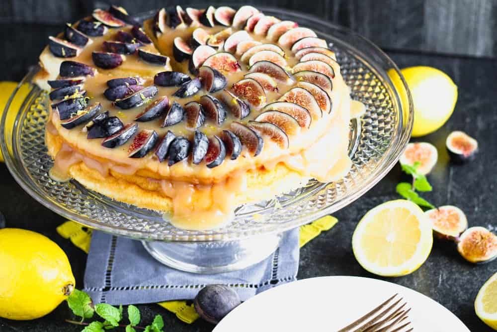 emon yogurt cake topped with honey caramel and quartered figs on a crystal cake pedestal with lemons and figs in the background
