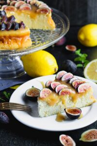 Closeup photo of a slice of lemon yogurt cake topped with honey caramel and quartered figs on a white plate with a crystal cake pedestal with the yogurt cake in the background along with lemons and figs