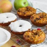Close up shot of pumpkin donuts with a heavy layer of cream cheese glaze on a cooling rack with more donuts before icing and apples in the background