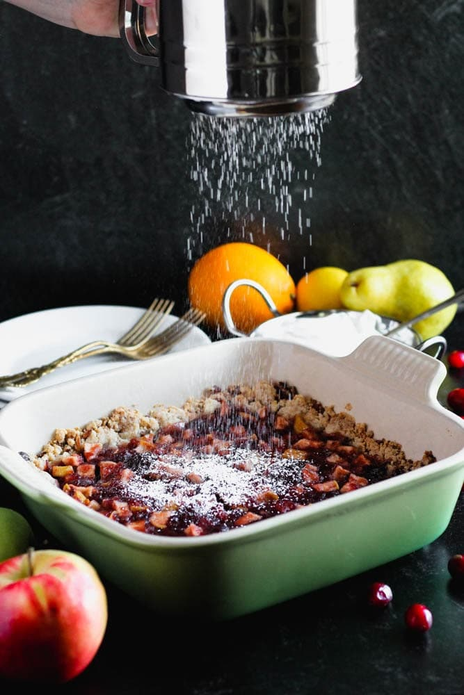 powdered sugar being sifted over the top of uncut pan of cranberry, apple and pear bars in a green baking dish with an apple in the foreground and an orange, pear and lemon in the background