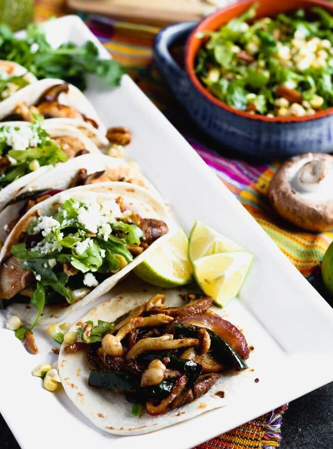 tacos filled with mushrooms and vegetables on a white platter with lime wedges