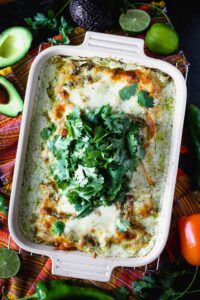 A rectangular casserole dish filled with a cheesy casserole topped with a pile of green cilantro leaves
