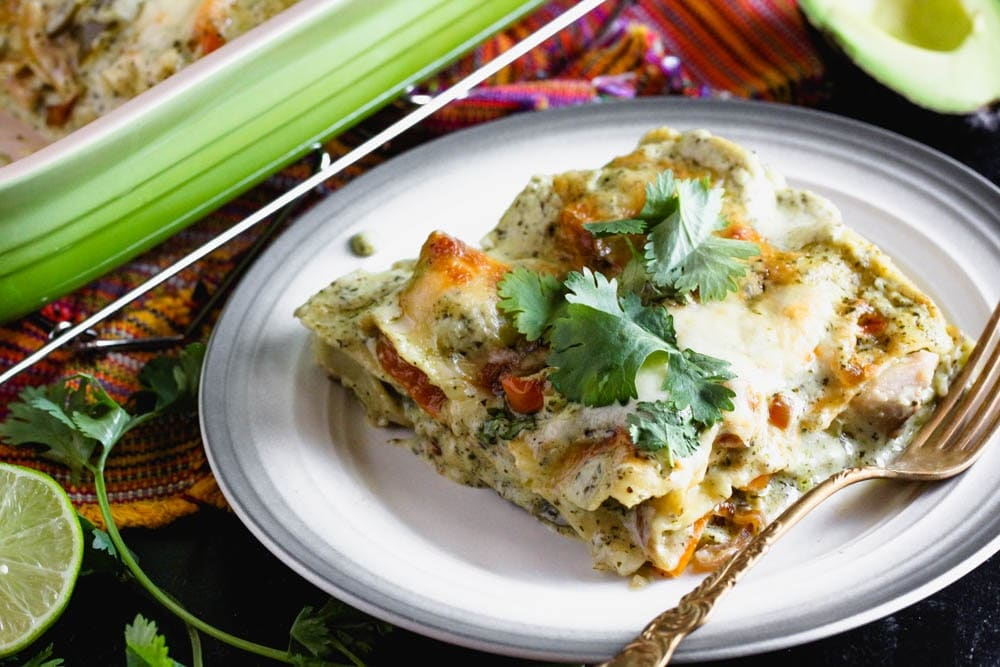 a square portion of lasagna with white sauce garnished with cilantro leaves