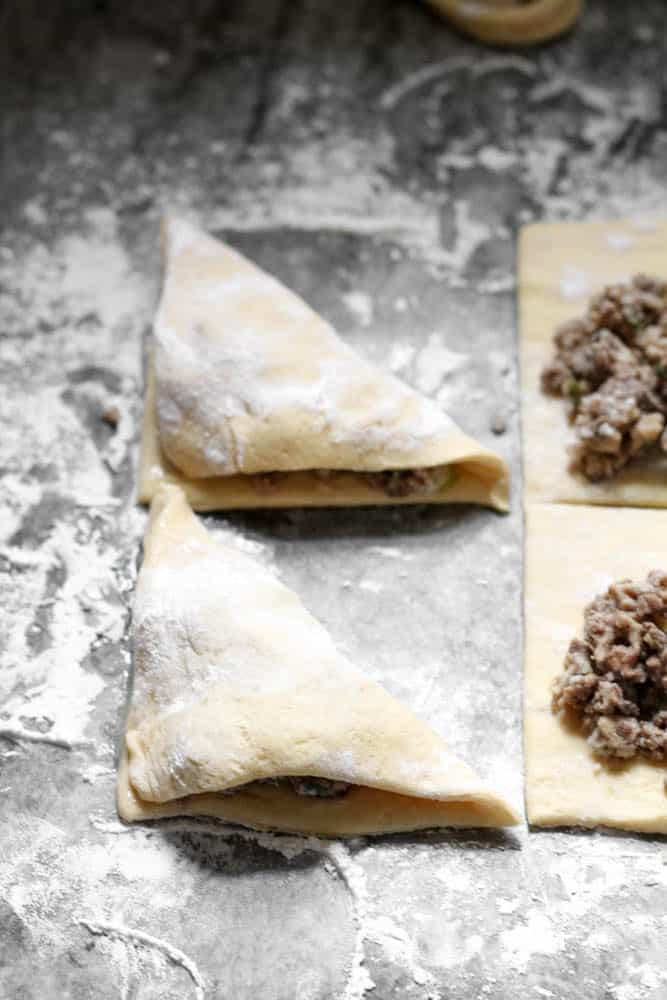 Two sheets of unbaked dough filled with crumbled beef