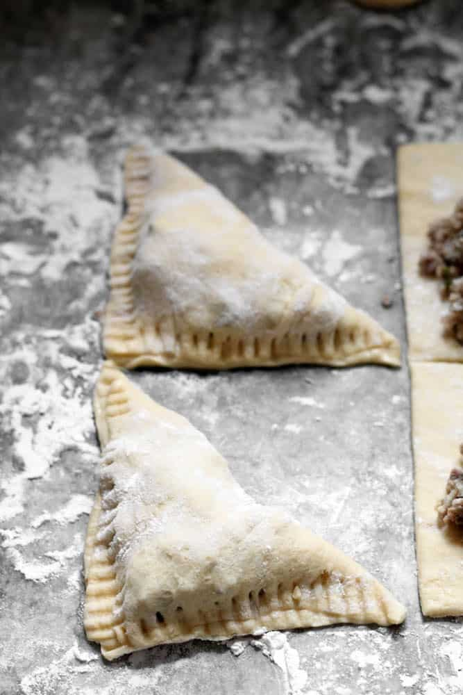 Two uncooked stuffed triangle shaped pastries on a floured surface