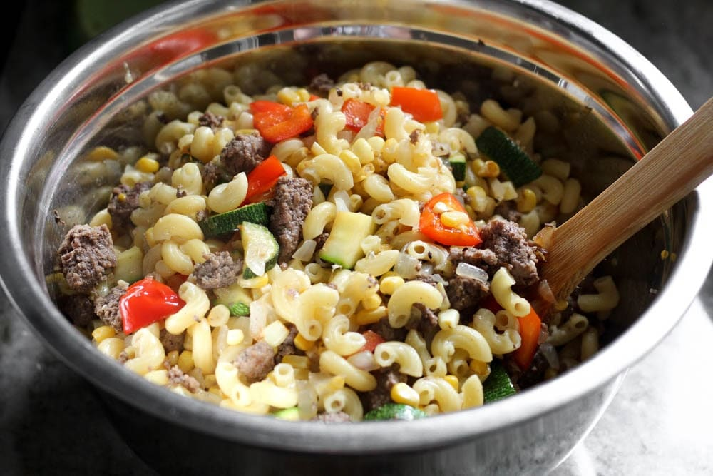 elbow macaroni tossed with browned ground sausage, zucchini, corn, onion, and red bell pepper in a metal mixing bowl