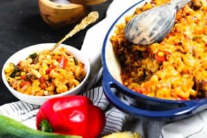 a pasta, squash, corn, and red pepper casserole in a blue baking dish with a serving of the casserole in a bowl to the side