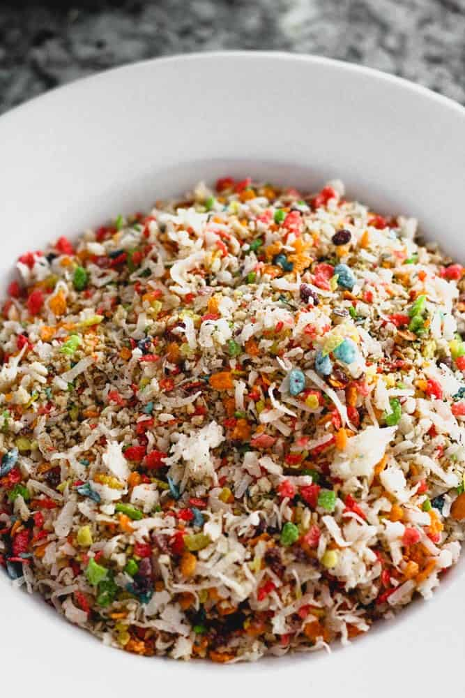 a white bowl filled with coconut flakes and multicolored cereal bits